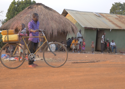NFS Uganda - Boy on with bike in village