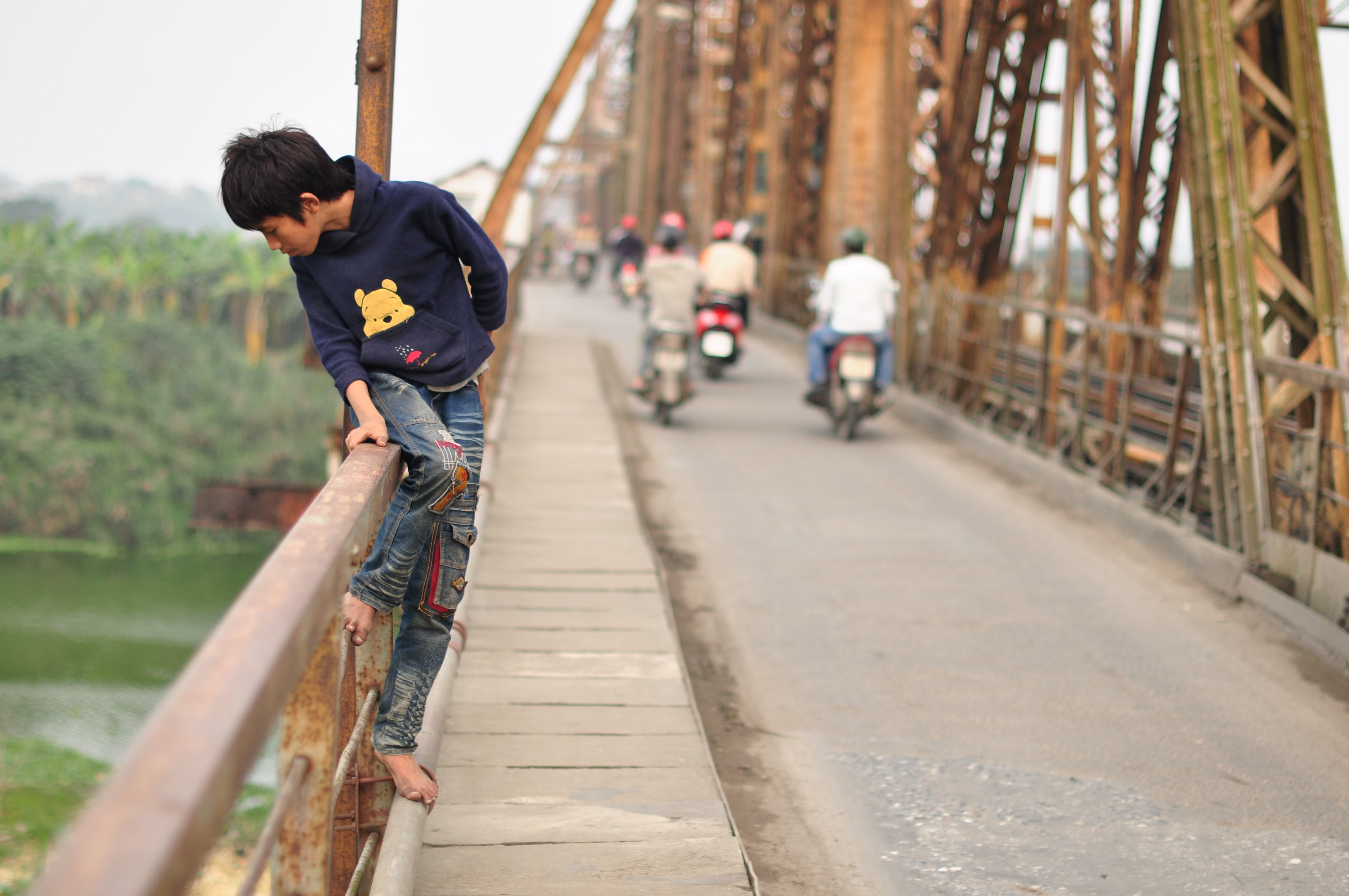 Young boy in Vietnam looking over a bridge where those vulnerable to human trafficking sleep